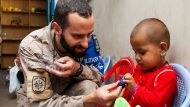 An International Security Assistance Force member gives a toy to an Afghan child July 11 at the Kabul Female Prison and Detention Center in Kabul, Afghanistan.  ISAF members donated school supplies, toys, soccer balls and women's clothing to the facility. (U.S. Air Force photo by Staff Sgt. Nestor Cruz) (released)
