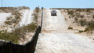 A Border Patrol agent on June 17, 2006, passes new vehicle barriers built by members of the 133rd Engineer Company, Wyoming National Guard, on the border with Mexico south of Deming, N.M. In Operation Jump Start, 6,000 National Guard troops are scheduled to help Border Patrol agents secure the border in four states. (U.S. Army photo by Sgt. Jim Greenhill) (Released)