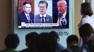 "People watch a TV screen showing file footage of U.S. President Donald Trump, right, South Korean President Moon Jae-in and North Korean leader Kim Jong Un, left, during a news program at the Seoul Railway Station in Seoul, South Korea, Wednesday, April 18, 2018. Trump has given his ""blessing"" for North and South Korea to discuss the end of the Korean War at their summit next week amid a diplomatic push to end the North Korean nuclear standoff. The signs read: "" Summit meeting between South and North Korea, the United States and North Korea ."" (AP Photo/Ahn Young-joon)"