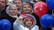 Turkey's EU Accession. A child and two older women hold turkey balloons.