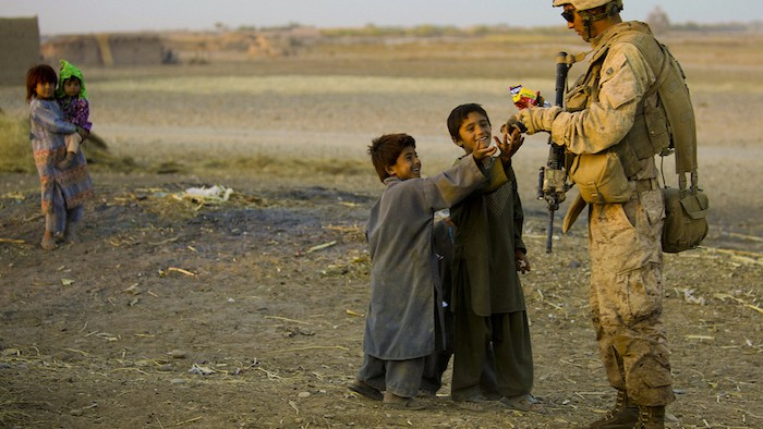 Seaman 3rd Class Eric Nobriga, assigned to Combined Anti-Armor Team 2, hands candy to Afghan children during a patrol in Nawa District, Helmand province, Afghanistan. 1st Battalion, 5th Marine Regiment is one of the ground combat elements deployed with Regimental Combat Team 7, whose mission is to conduct counterinsurgency operations in partnership with the Afghan national security forces in southern Afghanistan.