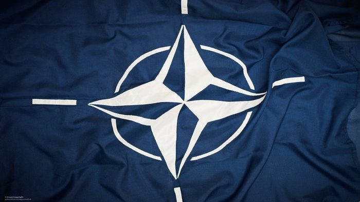 The flag of NATO.  The flag of the North Atlantic Treaty Organization (NATO) consists of a dark blue field charged with a white compass rose emblem, with four white lines radiating from the four cardinal directions.   Adopted three years after the creation of the organization, it has been the flag of NATO since October 14, 1953. The blue colour symbolizes the Atlantic Ocean, while the circle stands for unity. ------------------------------------------------------- © Crown Copyright 2014 Photographer: Sergeant Paul Shaw LBIPP (Army) Image 45157525.jpg from www.defenceimages.mod.uk    Use of this image is subject to the terms and conditions of the MoD News Licence at www.defenceimagery.mod.uk/fotoweb/20121001_Crown_copyright_MOD_News_Licence.pdf   For latest news visit www.gov.uk/government/organisations/ministry-of-defence Follow us:  www.facebook.com/defenceimages www.twitter.com/defenceimages