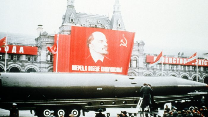 A Soviet SSN-8 intercontinental ballistic missile is displayed beneath a picture of Lenin in Red Square.